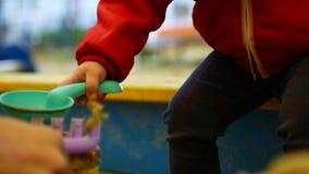 孩子接触沙子小雕象用他的手 特写镜头 女孩充当沙盒 影视素材