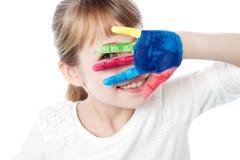 孩子掩藏的面孔用她色的手 库存照片