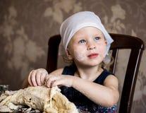 孩子揉在方巾的面团 免版税图库摄影