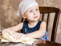 孩子揉在方巾的面团 免版税库存照片