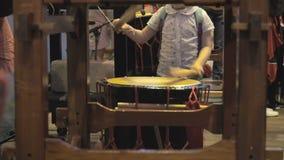 孩子播放鼓taiko 与鼓槌的一个孩子在他的手上在音乐会以后触击在阶段的鼓 股票录像