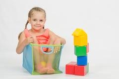 孩子攀登了沉溺于玩具的一个箱子 免版税库存照片