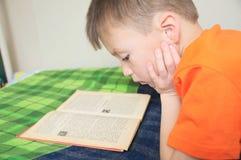 孩子教育,孩子说谎在床上的阅读书,严肃的孩子读了与书,教育,有趣的童话 免版税库存照片
