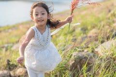 孩子时尚 逗人喜爱的矮小的亚裔女孩佩带的白色衣裳和花草在她的手上 免版税库存图片