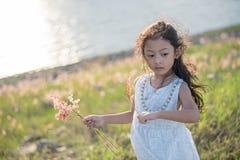 孩子时尚 逗人喜爱的矮小的亚裔女孩佩带的白色衣裳和花草在她的手上 库存照片