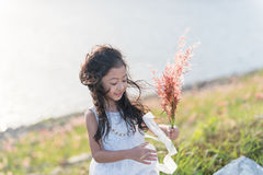 孩子时尚 逗人喜爱的矮小的亚裔女孩佩带的白色衣裳和花草在她的手上 免版税库存照片
