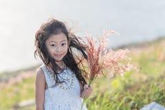 孩子时尚 逗人喜爱的矮小的亚裔女孩佩带的白色衣裳和花草在她的手上 库存图片