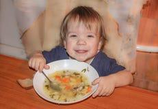 孩子是从板材的汤 一个小男孩吃他自己的汤 图库摄影
