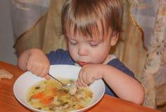 孩子是从板材的汤 一个小男孩吃他自己的汤 免版税库存照片