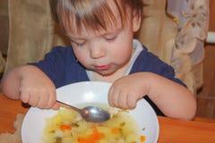 孩子是从板材的汤 一个小男孩吃他自己的汤 免版税库存图片