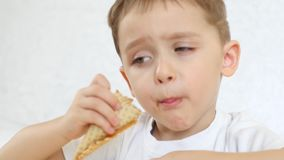 孩子是愉快吃冰淇凌巧克力锥体在奶蛋烘饼锥体的,在桌上,坐白色背景 关闭 股票视频