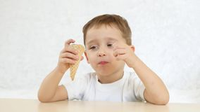 孩子是愉快吃冰淇凌巧克力锥体在奶蛋烘饼锥体的,在桌上,坐白色背景 股票视频