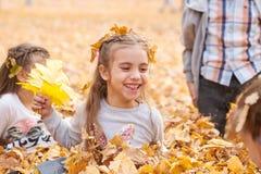 孩子是说谎和使用在落叶在秋天城市公园 免版税库存照片