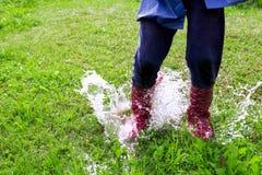 孩子是跳和使用在草的水池 库存图片
