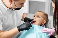 孩子是镇静和没惊吓安排他的牙出席由一位年轻男性牙医在一副白色T恤杉和黑手套 库存图片