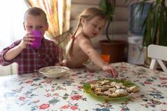 孩子是食用的兄弟姐妹早餐,牛奶,曲奇饼,生活方式 免版税库存照片