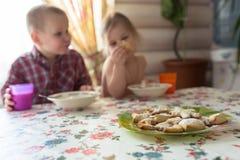孩子是食用的兄弟姐妹早餐,牛奶,曲奇饼,生活方式 免版税图库摄影