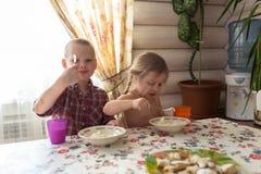孩子是食用的兄弟姐妹早餐,牛奶,曲奇饼,生活方式 库存图片