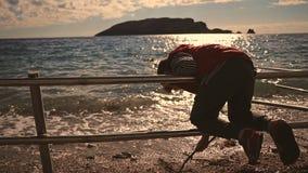 孩子是8岁 使用在海滩用在日落的一根棍子 股票视频