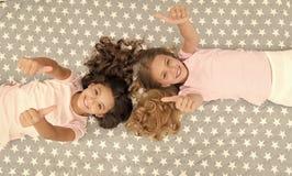 孩子显示赞许姿态 床顶视图的女孩孩子 睡衣派对概念 女孩要获得乐趣 ?? 免版税库存照片