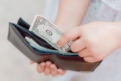 孩子有一个皮革钱包的女孩手,右手拉扯美国金钱美元USD 免版税库存照片