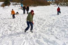 孩子有一次雪球战斗在白色多雪的区域 免版税库存图片