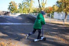 孩子有效地推挤沿路的滑行车 免版税图库摄影