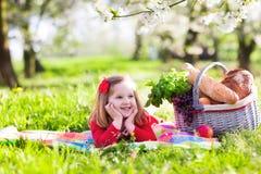 孩子有野餐在开花的庭院 免版税库存照片