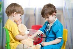 孩子有长毛绒玩具的戏剧医生 免版税库存照片