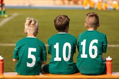 孩子橄榄球队 观看比赛的足球孩子 橄榄球足球孩子的比赛比赛 免版税图库摄影