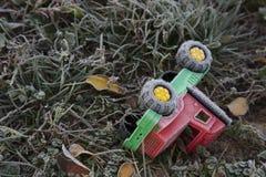 孩子汽车落入草和用霜盖 库存照片