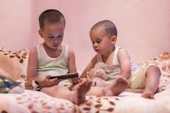 孩子演奏在卧室的手机,放松概念 在卧室观看在智能手机的两个弟弟一部动画片 免版税图库摄影