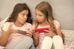 孩子演奏智能手机流动比赛应用 智能手机应用概念 少女休闲睡衣派对 ?? 免版税库存图片