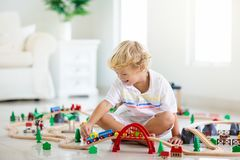 孩子演奏木铁路 有玩具火车的孩子 库存图片