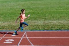孩子炫耀,孩子跑在体育场轨道的,训练和健身 免版税图库摄影