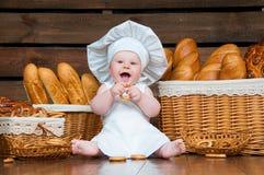 孩子烹调吃在篮子背景的一个百吉卷与卷和面包的 库存照片