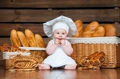 孩子烹调吃在篮子背景的一个百吉卷与卷和面包的 图库摄影