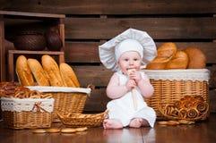 孩子烹调吃在篮子背景的一个百吉卷与卷和面包的 免版税库存图片