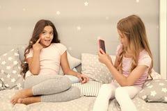 孩子照相射击录影 智能手机照片概念 少女休闲睡衣派对 女孩智能手机摆在伟大 库存图片