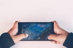 孩子特写镜头递打在手机的电子游戏 免版税图库摄影