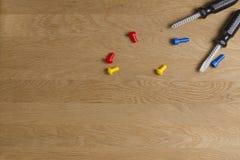 孩子玩具工具:塑料螺丝刀、螺丝和坚果在木背景 顶视图 平的位置 免版税图库摄影