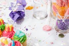 孩子生日聚会桌用杯形蛋糕和糖果 免版税图库摄影