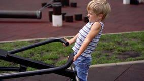孩子生活在一个现代城市-小男孩做着在模拟器的体育在运动场 股票录像