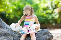 孩子用兔子 兔宝宝复活节 孩子和宠物 免版税库存照片