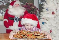 孩子用圣诞节曲奇饼 图库摄影