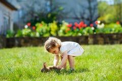 孩子用在草的一只兔子 免版税图库摄影