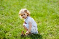 孩子用在草的一只兔子 库存图片
