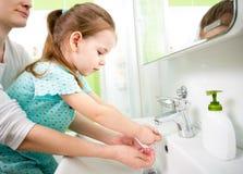 孩子用妈妈洗涤的手 免版税库存照片