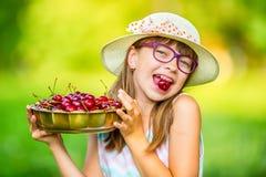 孩子用樱桃 小女孩用新鲜的樱桃 年轻逗人喜爱的白种人白肤金发的女孩佩带的牙括号和玻璃 库存图片