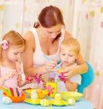 孩子用母亲油漆鸡蛋 图库摄影